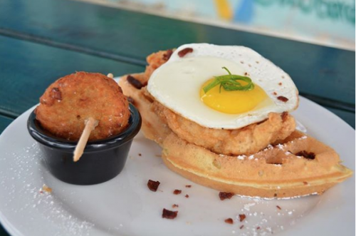 a plate with chicken topped on waffles with a fried egg on top of the chicken