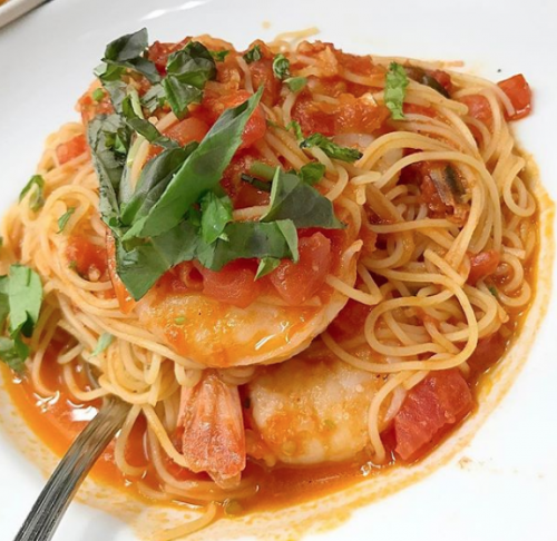 pasta with shrimp prawns sprinkled with basil on top