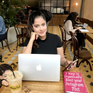 a girl in a coffee shop with brown hair in a pony tail with a laptop and iced coffee open.
